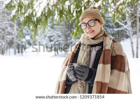 Waist up portrait of  smiling young woman in winter resort posing holding cup with hot cocoa and looking at camera, copy space