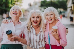 Waist up portrait of three laughing grannies walking around the city while holding coffee and hugging