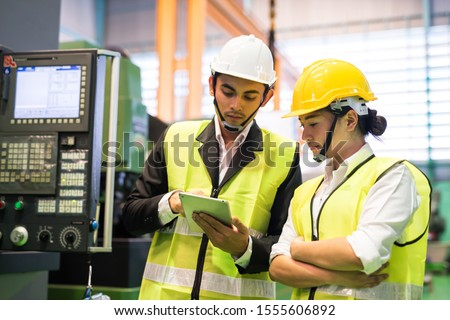 Waist up portrait of two Asian factory workers with safety helmet check stock in digital tablet near monitor of industrial machine. Manufacturing industry to produce car parts. Quality assurance (QA).