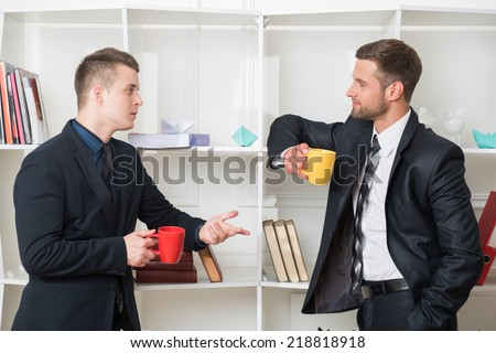 Waist-up portrait of two handsome businessmen in suits looking on each other while having a coffee-break in office standing near a bookshelf and discussing something