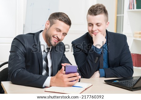 Waist-up portrait of two handsome businessmen in suits sitting at the table in office interior, one holding in his hands a mobile phone and both lightly laughing while looking on the screen of phone