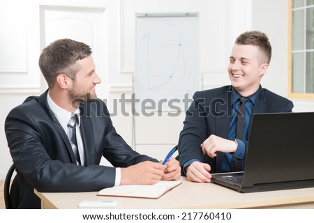 Waist-up portrait of two handsome businessmen in suits sitting at the table with laptop in office interior, laughing and looking on each other while discussing a new project