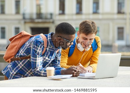 Waist up portrait of two international students doing homework together standing outdoors in campus, copy space Stockfoto ©