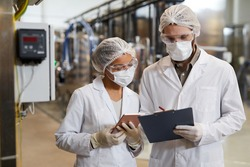 Waist up portrait of two workers wearing masks and lab coats while discussing production at chemical plant, copy space