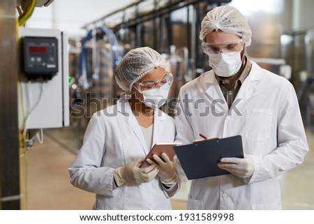 Waist up portrait of two workers wearing masks and lab coats while discussing production at chemical plant, copy space Foto stock ©