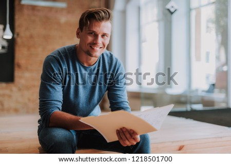 Waist up portrait of young happy designer is siting with new interesting project in his hands and smiling
