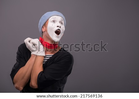 Waist-up Portrait of young male mime holding hands near his face like a girl and playfully looking aside and singing isolated on grey background with copy place