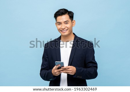 Waist up portrait of Young smiling handsome Asian man in semi formal suit using mobile phone in light blue isolated studio background
