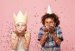 Waist up portyrait of two children blowing glitter at camera while standing against pink background, copy space