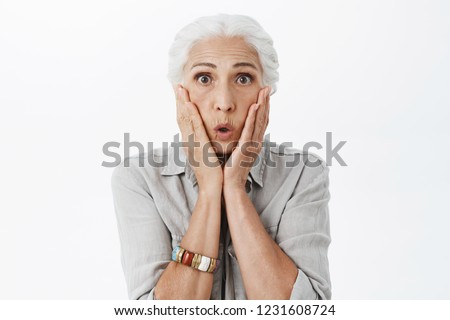 Waist-up shot of amazed and surprised emotive senior lady with grey hai folding lips in wow sound holding palms on face from amazement and interest posing impressed over white background