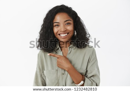 Waist-up shot of amused friendly-looking charming dark-skinned woman with curly hairstyle in grey shirt pointing left smiling joyfully at camera discussing interesting concept over white background #1232482810