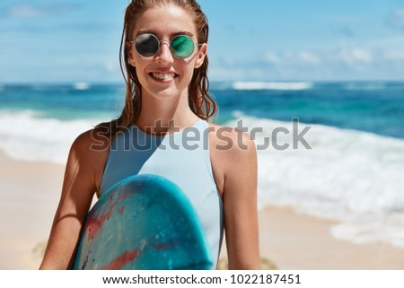 Waist up shot of beautiful glad young female surfer wears sunglasses and holds surf board, stands on sandy beach, being wet after surfing on waves, expresses positive emotions and satisfaction - Shutterstock ID 1022187451