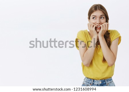 Waist-up shot of concerned nervous and anxious cute young timid woman in yellow t-shirt biting fingernails looking scared at upper left corner frightened, overreacting posing against white background #1231608994