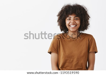 Waist-up shot of cute carefree friendly-looking African American teenage girl with afro hairstyle smiling broadly with shy and happy expression meeting new classmates over gray background