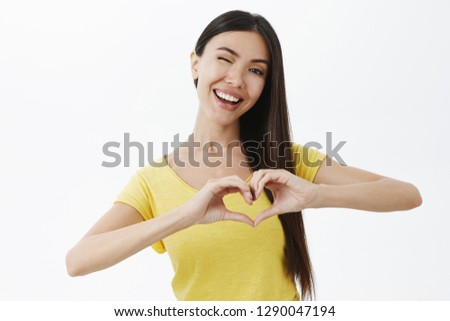Waist-up shot of cute caring and happy girlfriend with lond dark hair winking joyfully smiling showing heart gesture over chest expressing love and affection being tender and friendly over grey wall #1290047194