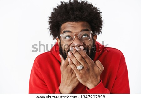 Waist-up shot of delighted happy african american male bearded friend in glasses chuckling, giggling with hand covering mouth looking up amused awaiting for prank come in action, joking over friend