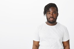 Waist-up shot of doubtful unimpressed dark-skinned man with stylish haircut, raising one eyebrown with doubt and staring seriously at camera, being careless and indifferent over white background