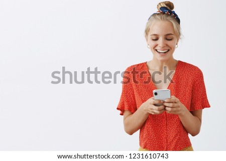 Waist-up shot of entertained attractive european woman in vintage blouse having fun and laughing over funny message while using smartphone over gray background joyfully gazing at cellphone screen