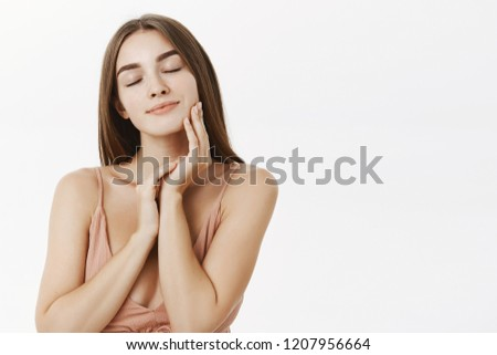 Waist-up shot of gentle and tender good-looking european girlfriend with beautiful facial features closing eyes and smiling sensually touching skin gently being delighted with skincare product #1207956664