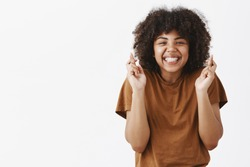 Waist-up shot of good-looking faithful and optimistic teenage african american girl with afro hairstyle crossing fingers for good luck and smiling joyfully praying for dream come true or making wish
