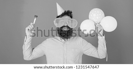 Waist up shot of good looking positive man with beard holding helium balloons and whistle smiling broadly, having fun on party. People, joy, entertainment and celebration concept. #1231547647