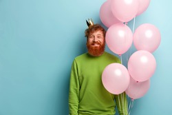 Waist up shot of handsome glad bearded man has birthday party, happy to recieve congratulations from friends, carries flying air balloons, has unforgettable festive event in life, stands indoor