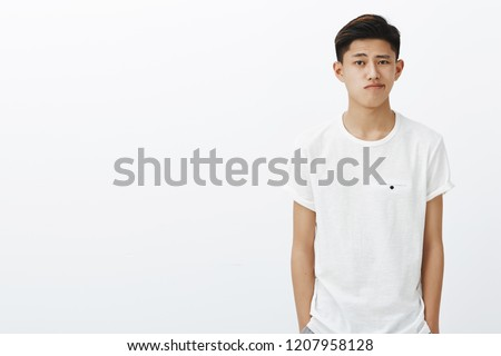 Waist-up shot of handsome stylish korean guy in white t-shirt holding hands in pockets smirking standing in normal pose wasting time, feeling gloomy and uncertain posing against white background