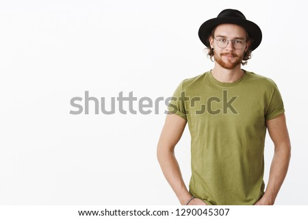 Waist-up shot of handsome upbeat boyfriend in hat, glasses with tattoos, beard and piercing holding hands in pockets smiling joyfully, enjoying fine coffee in cafe, posing delighted over gray wall