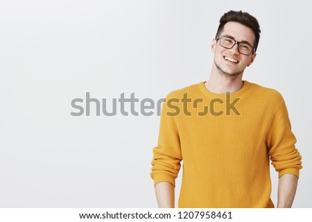 Waist-up shot of happy and delighted handsome young man in glasses and yellow sweater tilting head, smiling and laughing as looking friendly at camera on right side of copy space over gray background