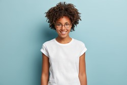 Waist up shot of happy curly woman with toothy smile, wears optical glasses and casual solid white t shirt, expresses good emotions, enjoys nice day, isolated over blue background. Face expressions