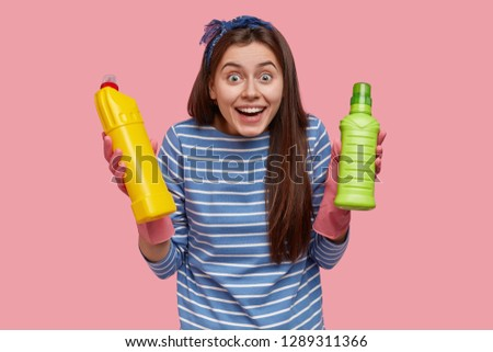 Waist up shot of happy European woman with cheerful expression wears striped clothes, carries bottles with cleaning supplies, looks joyfully, models against pink background. Home cleaning concept #1289311366