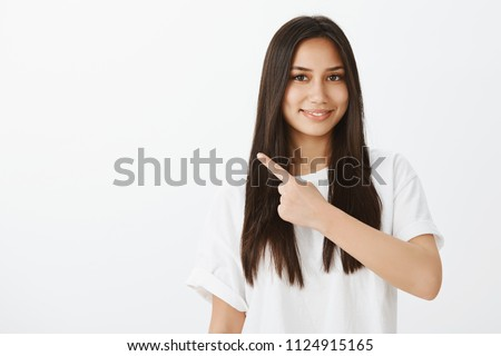 Waist-up shot of pleased charming female student in white t-shirt, pointing at upper left corner and smiling cheerfully, standing over gray background while directing at perfect place to hang out