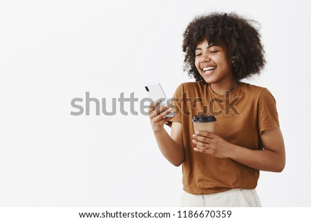 Waist-up shot of pleased friendly and attractive dark-skinned female model with curly hair holding paper cup of coffee and smartphone laughing out loud while readin funny story in cellphone #1186670359