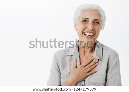 Waist-up shot of pleased grateful charming granny in shirt holding palm on chest and smiling broadly at camera being satisfied and delighted and son achievements standing happily over gray background