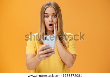 Waist-up shot of shocked and stunned emotive young woman reacting to shocking terrible news reading online from internet gasping opening mouth nervously touchin cheek staring at smartphone screen