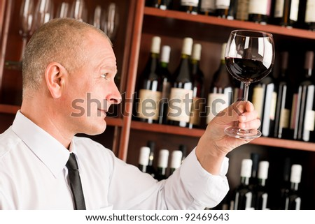Waiter at bar hold glass of red wine in restaurant