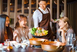 waiter  bring  vegetables for hot pot  and serving group of friends in restaurant