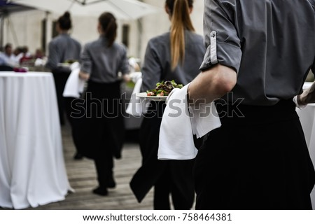 Waiter carrying plates with meat dish on some festive event #758464381