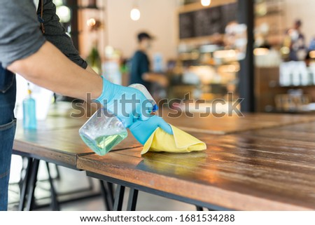 Waiter cleaning table with disinfectant spray and Microfiber cloth in cafe covid-19 preventing.