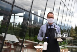 Waiter cleaning the table with Disinfectant Spray in a restaurant wearing protective medical mask and gloves new normal concept