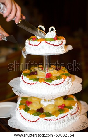 waiter cutting beautiful Wedding Cake with knife