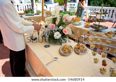 stock photo Waiter filling glasses of champagne during wedding buffet