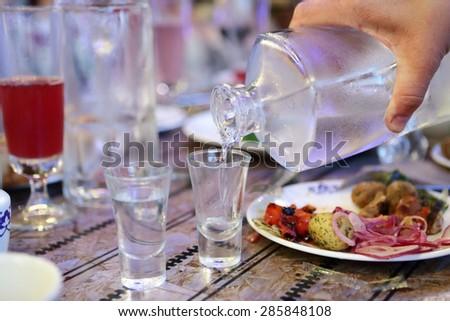 Waiter filling vodka in the russian restaurant