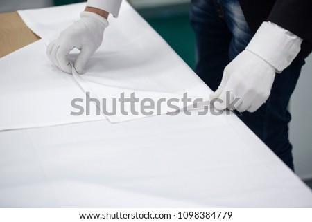 Waiter folds and folds napkins