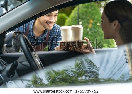 Waiter giving hot coffee cup with disposable tray and bakery bag through car window to customer at drive thru service station. Drive thru is popular service after coronavirus covid-19 pandemic. Foto stock ©