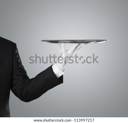 Waiter holding empty silver tray over gray background with copy space ストックフォト ©