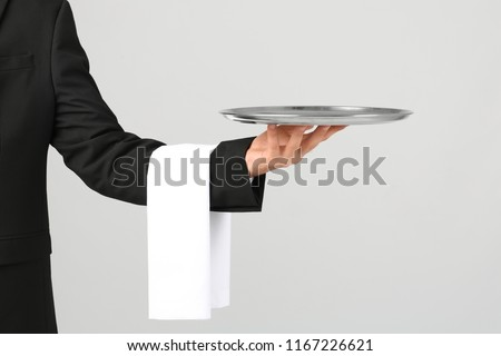 Waiter holding metal tray on light background ストックフォト ©