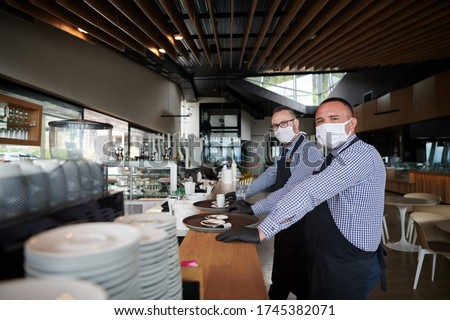 waiter in a medical protective mask serves  the coffee in restaurant durin coronavirus pandemic representing new normal concept