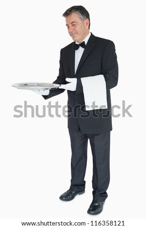 Waiter in suit offering something on silver tray with towel over his arm