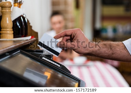 Waiter Inserts The Card Into A Computer Terminal, Against Visiting The Restaurant
